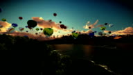 Air balloons flying above lake surrounded by mountains, beautiful sunset, tilt video