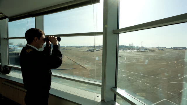 Air traffic controller is looking into distance in airport with binoculars video