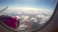 Aircraft flying near clouds sunny flight, wing turbine blue sky. Airplane flying high above ground carrying passengers, airliner wing turbine and clouds in porthole, air plane interior shot, international jet flight transportation, daytime sky video