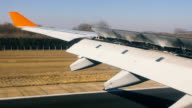 Aircraft move by air strip at airport, wing view from the inside video