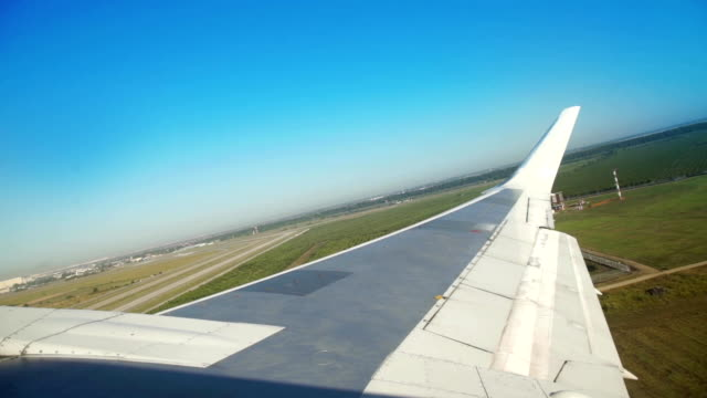 Aircraft wing window view while airplane taking off from airport video