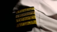 Aircrew captain at work, closeup of pilot's shirt epaulets, career in aviation video