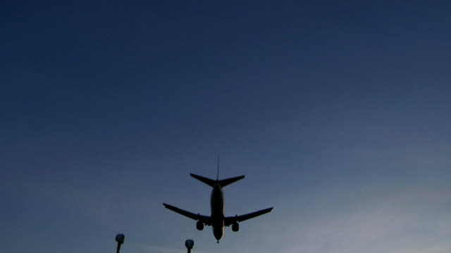 Airliner landing into the sunset video