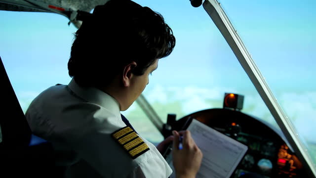 Airplane captain switching to autopilot mode, writing flight details in document video