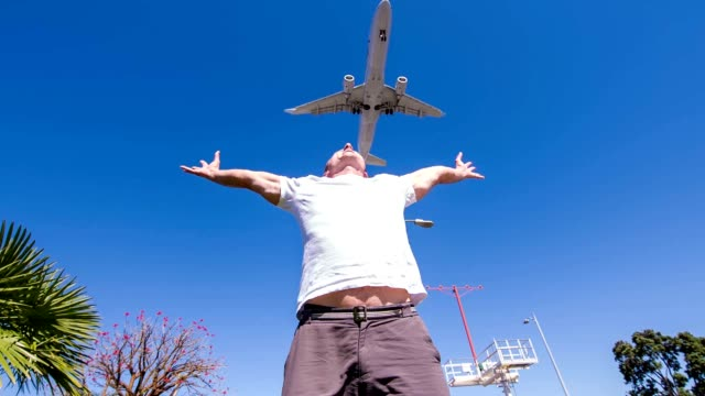 SLO MO Airplane flying above one mid-adult man video