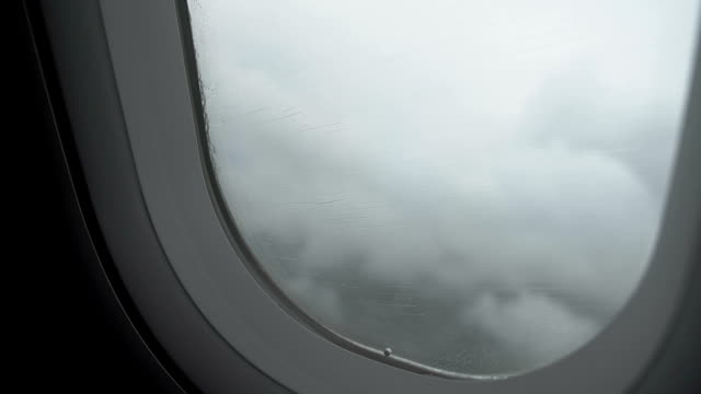 Airplane flying into turbulence zone with stormy clouds, rain on window, danger video