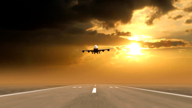 airplane landing against sunset background video