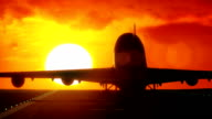 Airplane lands on airport runway with sunset / sunrise HD video