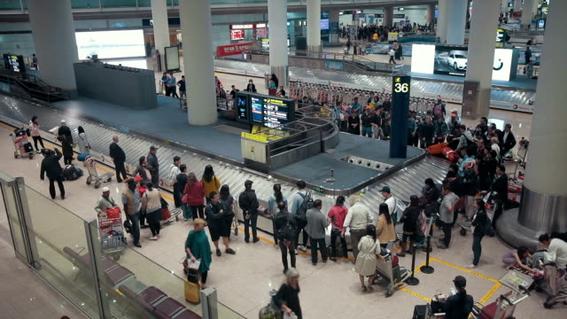 Airplane travelers are waiting for their luggage from a conveyor belt at Beijing International Airport,China video