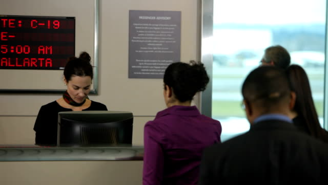 Airport passengers check in at ticket counter video