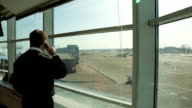 Airport Security Officer in uniform watching aerodrome traffic and talking on phone video