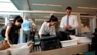 Airport travelers gather belongings after baggage screening video