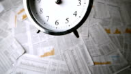 Alarm clock falling over sheets of paper video