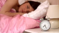 Alarm clock ringing and waking a sleeping woman video