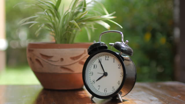 Alarm Clock with green plant on wooden table with green bokeh background , dolly shot right to left video