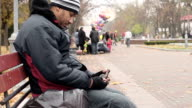 Alcohol addict sitting on bench in park with beer bottle, poor lifestyle choices video