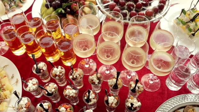 Alcohol in the glasses, juice, salads, canapés and fruit for catering video