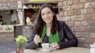 Alfresco coffee, sidewalk cafe and smile to camera. video