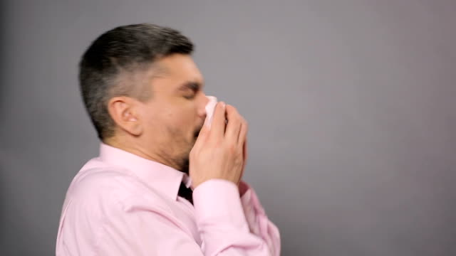 Allergy, rhinitis, sickness. Diseased male sneezing and wiping nose with tissue video