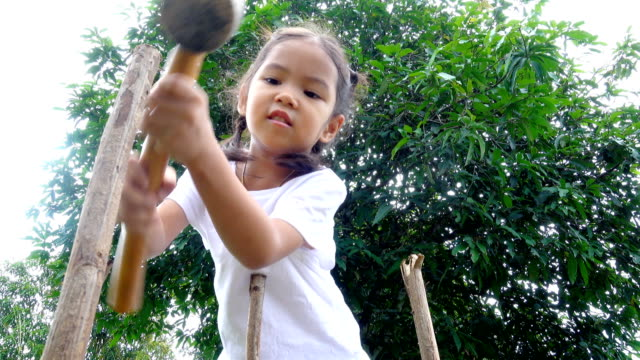 Alone children girl hammering poles for protect young tree to her planting. Eco environmental conservation concept video