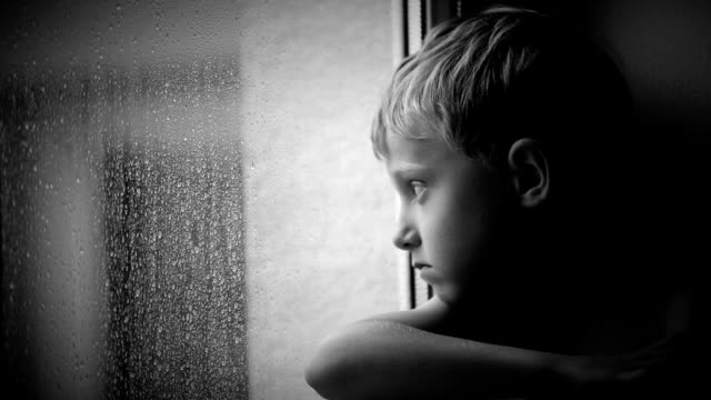 Alone little boy looks raindrops through window glass video