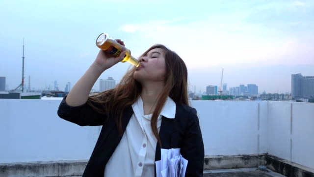 Alone young asian  businesswoman in depression, drinking alcohol video