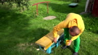 amateur worker boy painting wood surface with brush in yellow color. Closeup. FullHD video