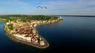 Amazing flight with birds over old city Piran in Slovenia, aerial panoramic view of St. George's Parish Church, old houses, roofs, fortress and the sea. video