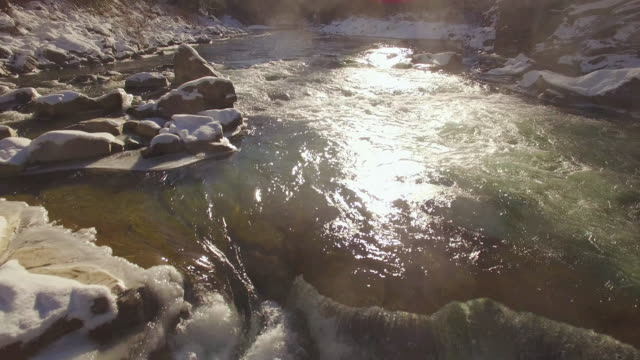 Amazing Lighting on Icy Raging River with Drone Flying Backwards Over Whiter Water Rapids and Fresh Powder Snow on Rocks video