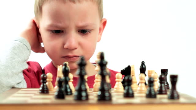 Ambitious little boy playing chess. video
