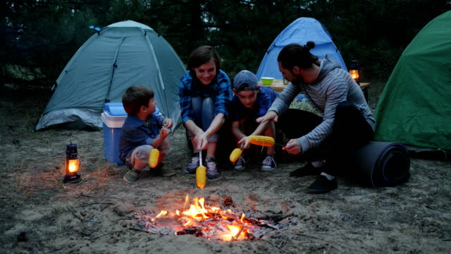 American family Sit around fire fry yellow corn, family evening picnic outdoors, mom, children and dad during summer holidays video
