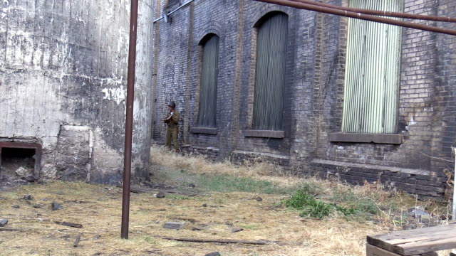 American World War 2 GIs advance through industrial buildings video