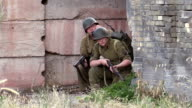 American World War 2 GIs crouch and hide outside  urban derelict building video