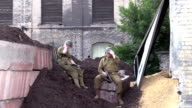 American World War 2 GIs relax outside urban derelict building video