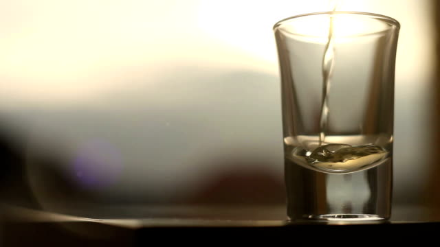An act of pouring a golden drink to the glass on the sunset background video