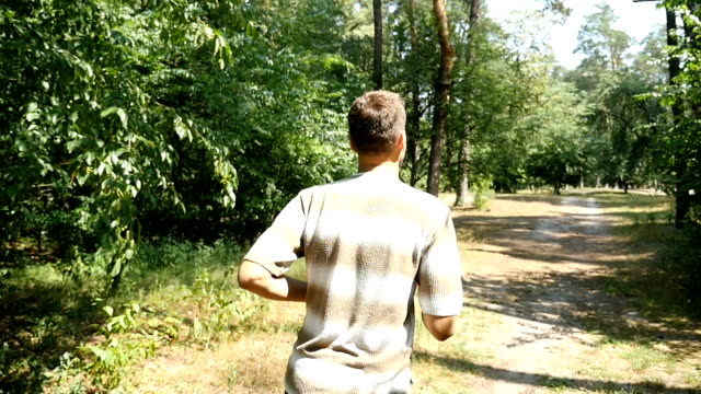 An active man in striped t-shirt and black pants runs in a forest in slow motion video