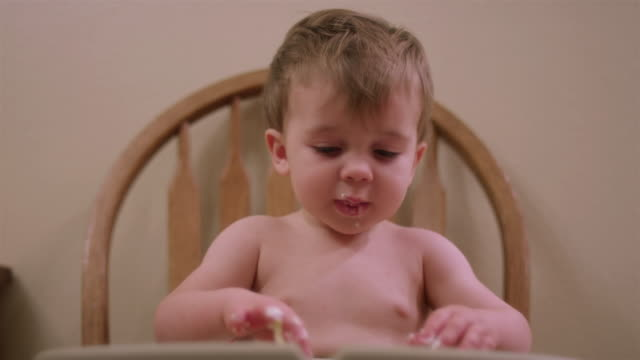 An adorable little boy in a high chair booster seat eating messy food with his hands video