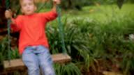 An adorable little boy swinging on a swing outside in slowmo video
