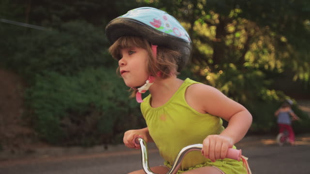 An adorable little girl happily riding her tricycle video