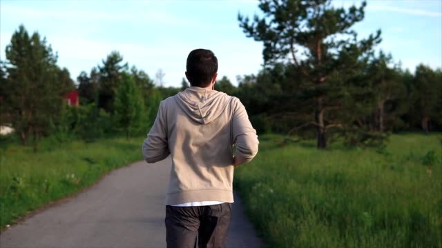 An adult male in a sport suit runs along a walking path in park on a summer day video