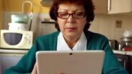 An adult woman with a glasses is using iPad video