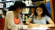An African American and Middle Eastern female high school STEM students studying together in library video