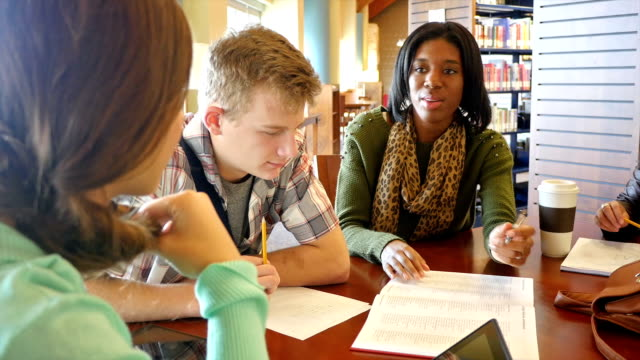 An African American young woman teaches or tutors a group of home school high school students in public library video