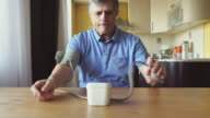 An aged man measuring the blood pressure at home video