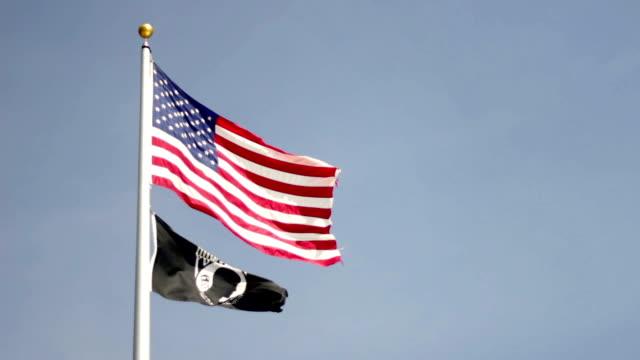 An American flag flowing with a Vietnam POW MIA Flag video