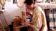 An artist checking her paint with her brushes video