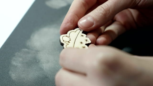 An artist looks at grinded wooden craft on sandpaper video