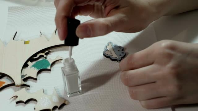 An artist paints on wooden craft video
