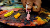 An artist squeezes out some pink paint from a tube of oil paint video