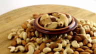 An assortment of nuts on wooden table.  Almond, cashew and brazilian nuts video